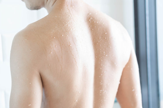 Closeup back of handsome asian man taking a shower in the bathroom, selective focus