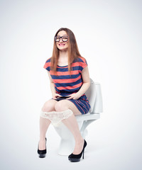 Happy young girl in glasses and a smartphone in her hands sitting on the toilet. Situation concept.