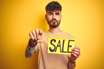 Young man with tattoo holding sale banner standing over isolated yellow background pointing with finger to the camera and to you, hand sign, positive and confident gesture from the front