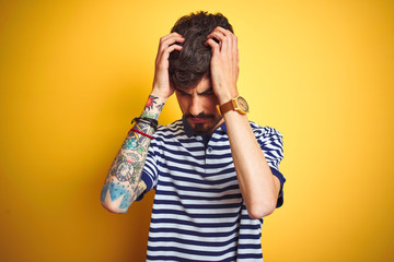 Young man with tattoo wearing striped polo standing over isolated yellow background suffering from headache desperate and stressed because pain and migraine. Hands on head.