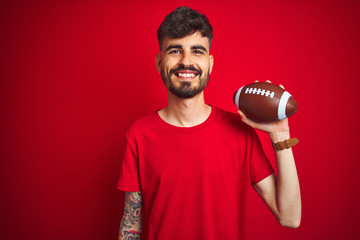 Young athlete man with tattoo holding football ball standing over isolated red background with a happy face standing and smiling with a confident smile showing teeth