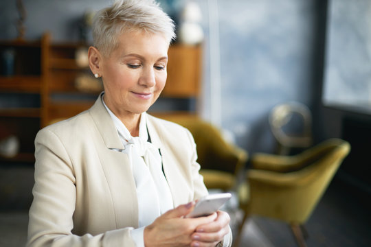 Close up image of beautiful confident mature businesswoman sitting at her office typing text message using online messenger on mobile phone or scrolling newsfeed via social network, smiling
