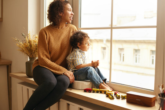 Cozy scene of joyful young Latin female wearing jeans and knitted jumper sitting on windowsill hugging her cute chubby little child, both watching outside, talking, having dreamy thoughtful expression