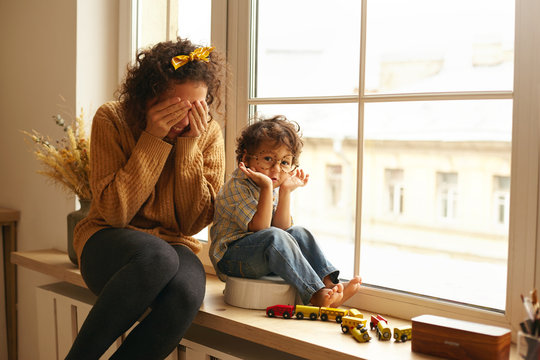 Cozy scene of happy family indoors. Attractive young female with curly hair enjoying sweet moments of maternity, sitting in large windowsill, playing seek and hide with adorable infant child