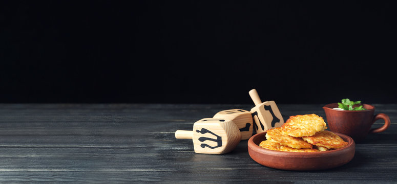 Dreidels and potato pancakes for Hanukkah on table against dark background with space for text