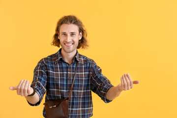 "Handsome man showing ""come here"" gesture on color background"