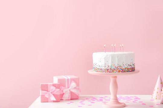 Tasty Birthday cake with gifts on table against color background