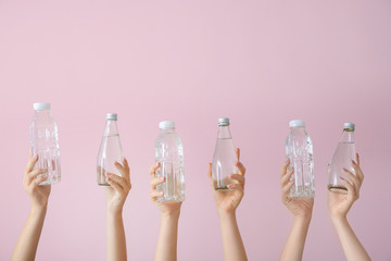 Female hands with bottles of water on color background