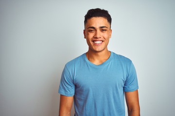Young brazilian man wearing blue t-shirt standing over isolated white background with a happy and cool smile on face. Lucky person.