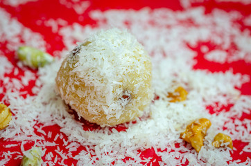 Coconut powder sprinkled Semolina Ladoo on a red plate with fried dry fruits