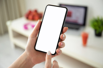 female hands holding phone with isolated screen in a room
