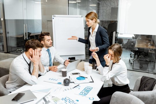 Female top manager or team leader quarreling at employees, dissatisfied with their work during a conference in the meeting room