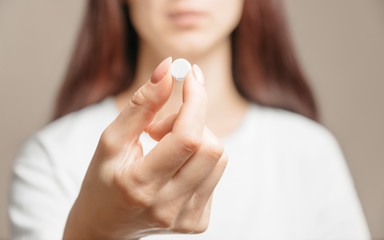 Woman holding a white round pill or vitamin.