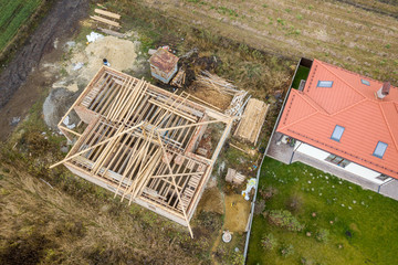 Top down aerial view of two private houses, one under construction with wooden roofing frame and another finished with red tiled roof.
