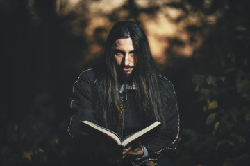 A man with long hair and beard in a black cloak in the image of a sorcerer warlock on Halloween. Dark magician the man in the background of the forest. A wizard in a dark forest with a magic book .