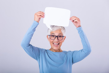 Cheerful mature woman holding speech bubble sign over her head and smiling. Happy senior lady with...