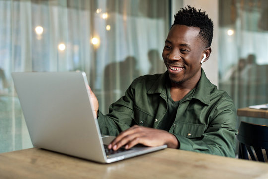 Handsome african american man using computer and smiling. young businessman recording video for online webinar using laptop