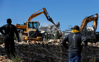 People watch as an Israeli machinery demolishes an under-construction Palestinian house near Hebron in the Israeli-occupied West Bank