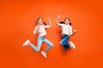 Full length photo of positive cute two children girls jump celebrate victory in school contest...