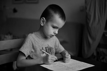 Little boy learns to write homework