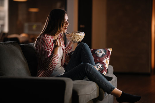 Young woman at home. Beautiful woman sitting in living room watching movie.