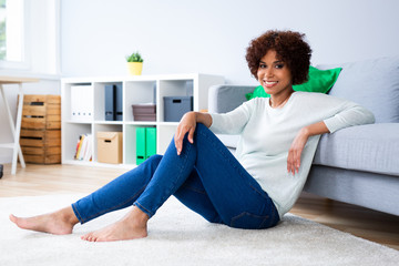 Portrait of beautiful young woman smiling at camera sitting on floor at home