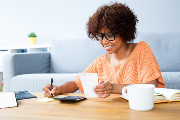 Young woman sitting taking care of bills and home finances while sitting in living room