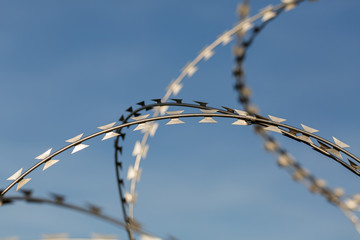 OBERPFAFFENHOFEN, BAVARIA / GERMANY - Sept 28, 2019: Detail of / isolated view on sharp, metallic razor wire / barbed wire. Blue sky in the background. Symbol for border, limiting migration, prison.