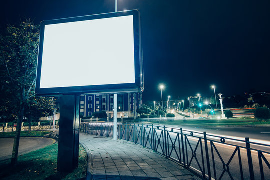 Square billboard mockup with blank canvas screen at night in the city.
