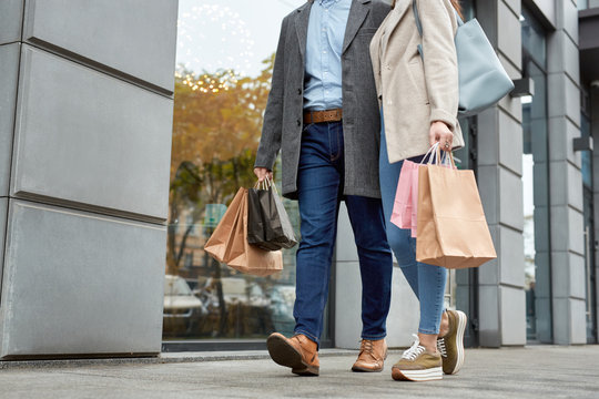 Adult woman and man walking together with shopping bags