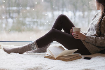 Thoughtful young brunette woman with morning cup of coffee looking through the window, blurry winter outside.