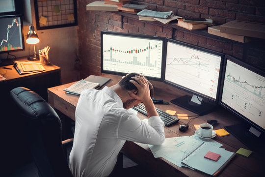 Young male trader at office work concept hard-working person
