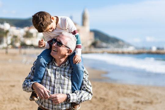 Happy senior man smiling joyfully piggybacking his cute little grandson at the beach