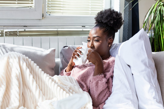 Sick woman has flu. Rhinitis, cold, sickness, allergy concept. Pretty sick woman has runnning nose, rubs nose with handkerchief and drinking hot beverage.