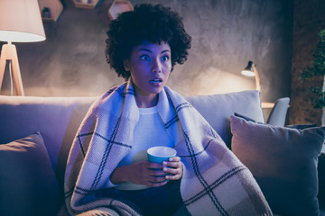 Unbelievable series concept. Astonished afro american girl sit couch watch film hold cup coffee look voiceless covered with checkered plaid blanket in house evening indoors