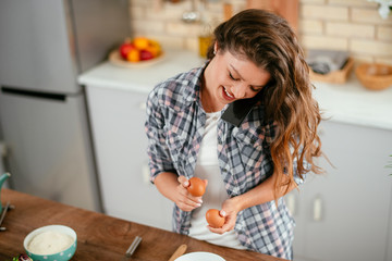 Young woman in kitchen. Beautiful woman taking on phone while cooking.