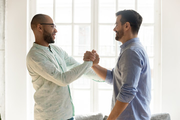 Mixed race male friends in eyewear shaking hands.