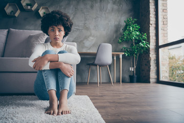Photo of pretty dark skin curly lady sitting floor near sofa sad eyes full of fear hold knees near chest afraid to be alone home wear casual sweater jeans outfit flat indoors