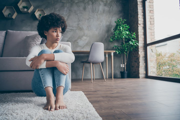 Photo of pretty dark skin curly lady sitting floor near sofa sad missing boyfriend looking window offended wear casual sweater jeans outfit flat indoors