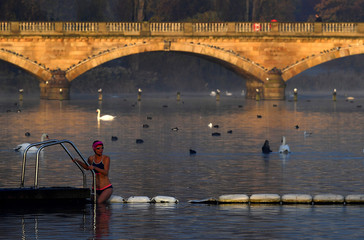 A swimmer enters the water during the early morning at the Serpentine lake in Hyde Park, London