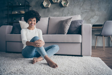 Fototapete - Photo of amazing dark skin curly lady sitting comfortable floor carpet near sofa amazing free time at home wear casual pullover jeans clothes flat indoors