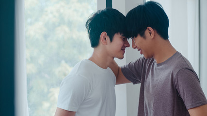 Asian Gay couple standing and hugging near the window at home. Young Asian LGBTQ+ men kissing happy relax rest together spend romantic time in living room at modern house in the morning concept.