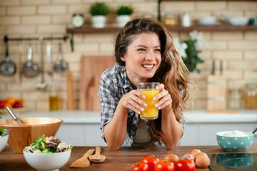 Young woman in kitchen. Beautiful woman in modern kitchen drinking orange juice.