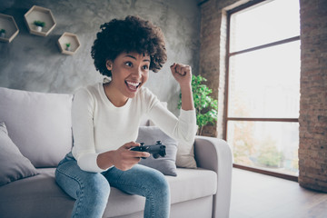 Photo of funny dark skin curly lady playing video games addicted want winning hold joystick triumphing football match sitting cozy couch wear casual sweater jeans outfit flat indoors