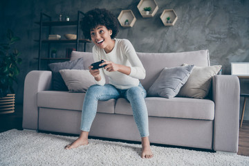 Fototapete - Photo of funny dark skin curly lady playing video games addicted want winning hold joystick sitting cozy couch casual sweater jeans outfit flat indoors