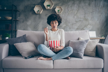 Fototapete - Photo of pretty dark skin wavy lady eating popcorn watching frightening horror film open mouth scary moment sitting cozy couch casual sweater jeans outfit flat indoors