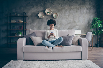Fototapete - Photo of pretty dark skin curly lady homey domestic atmosphere texting telephone with friends reading instagram posts sitting comfy couch casual outfit flat loft indoors