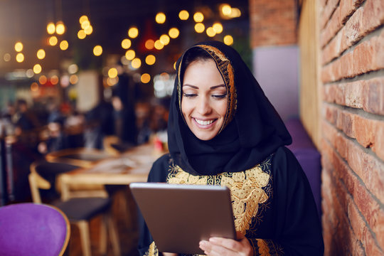 Gorgeous muslim woman dressed in traditional wear sitting in cafe and using tablet.