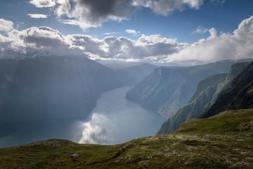 Sunburst with light beams lighting up fjord landscape Norway