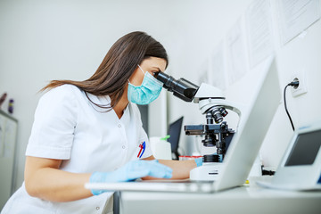 Charming caucasian laboratory assistant in white uniform, with protective mask and rubber gloves sitting in lab looking blood sample trough microscope and using laptop.